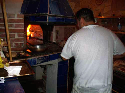 A pizza-maker in Italy at a pizzeria.